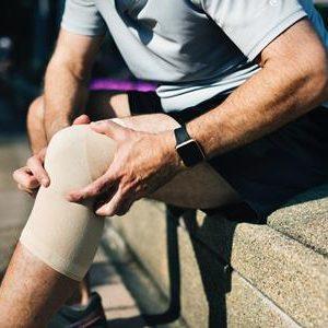 man holding sore leg